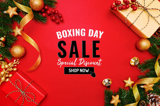 Boxing day sale with Christmas present and xmas decoration on red background stock photo