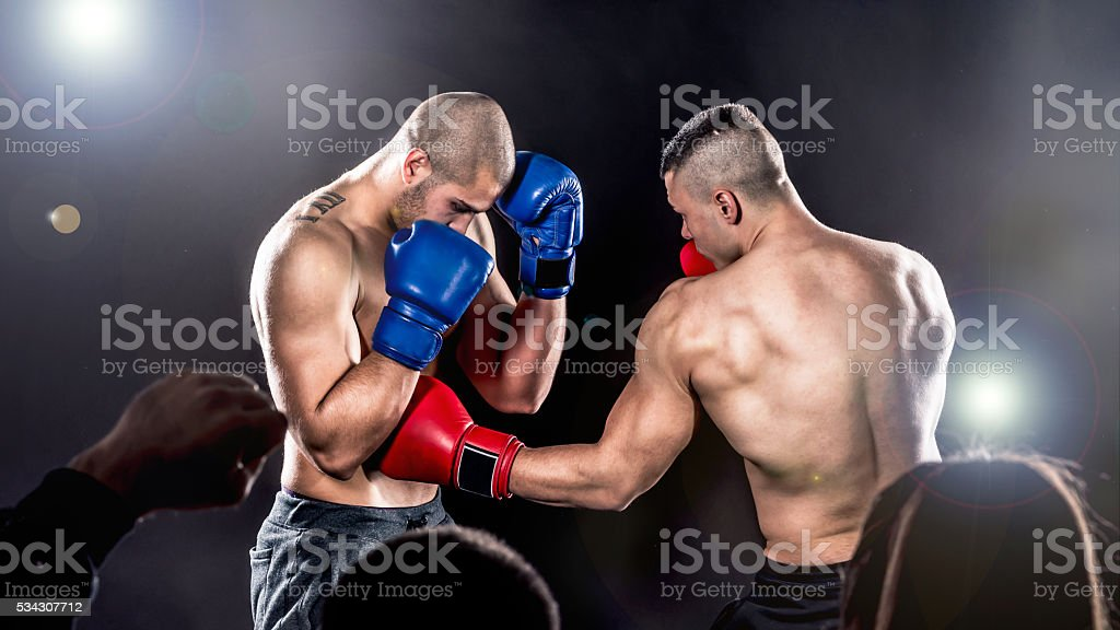 Boxing Fight Two Boxing Fighters on Boxing Match in front of Spectators Boxing - Sport Stock Photo