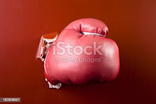 160558362 istock photo Boxing glove hand coming through wall. 182909557