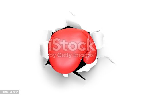 160558362 istock photo Boxing glove through a hole in paper 136376585
