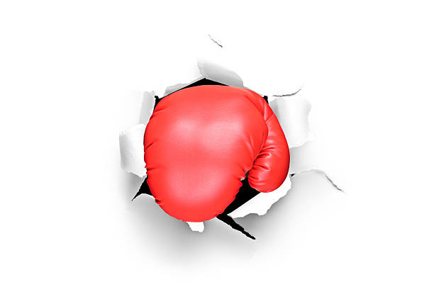 boxing glove through a hole in paper - punching stock photos and pictures