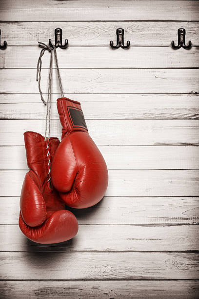boxing gloves hanging on wooden wall - sports glove stock photos and pictures