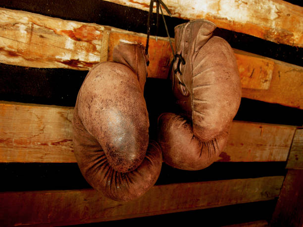 boxing gloves on the wall. old, vintage pair of leather mittens - mike tyson стоковые фото и изображения