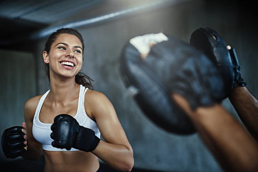 Shot of a young woman sparring with a boxing partner at the gym