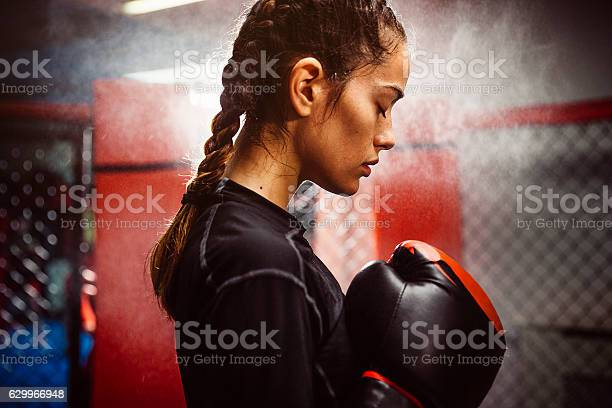 Female boxer in a boxing ring training. condensation, heat and sweat. Low lighting with a spot light in the background. Very real and gritty