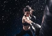 Young woman boxing at the punching bag