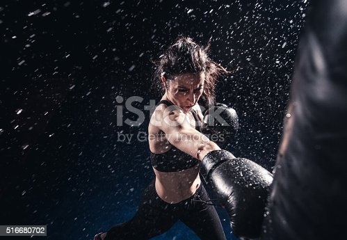 Young woman boxing at the punching bag