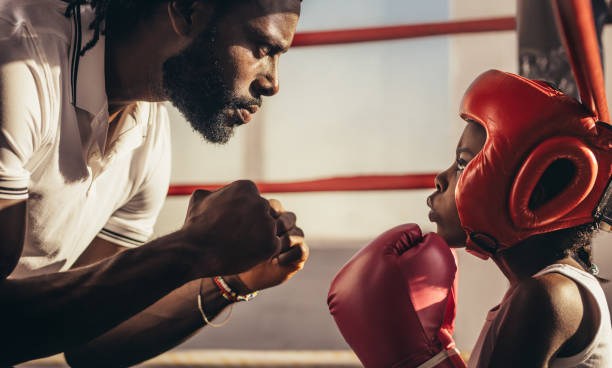 Boxing trainer teaching a kid about boxing stock photo