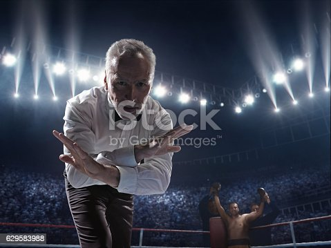 A picture of a boxer who made knock out to the opposite one. Referee counts. Sportsmen are on boxing ring with bleachers full of people