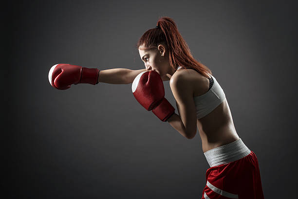Boxing woman during exercise-gray background stock photo