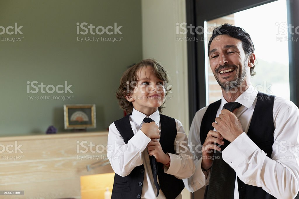 Boy adjusting tie while looking at father stock photo