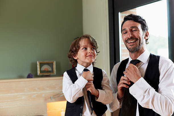 boy adjusting tie while looking at father - imitation stock photos and pictures