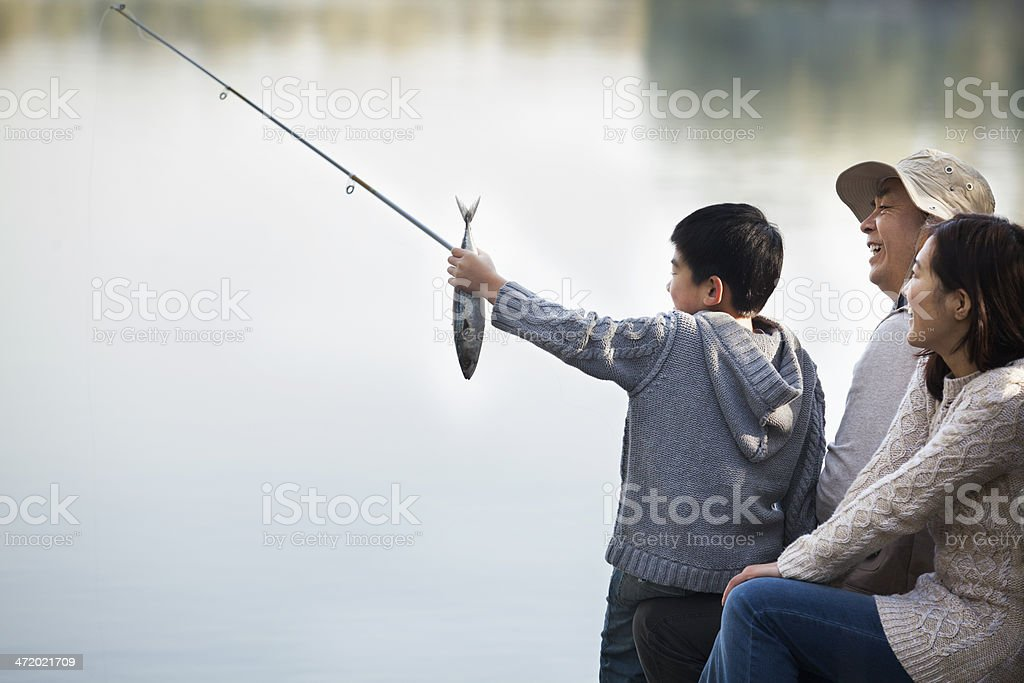 Boy admiring fishing catch with family at lake stock photo