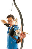 Boy with blue shirt and jeans shootling with a longbow