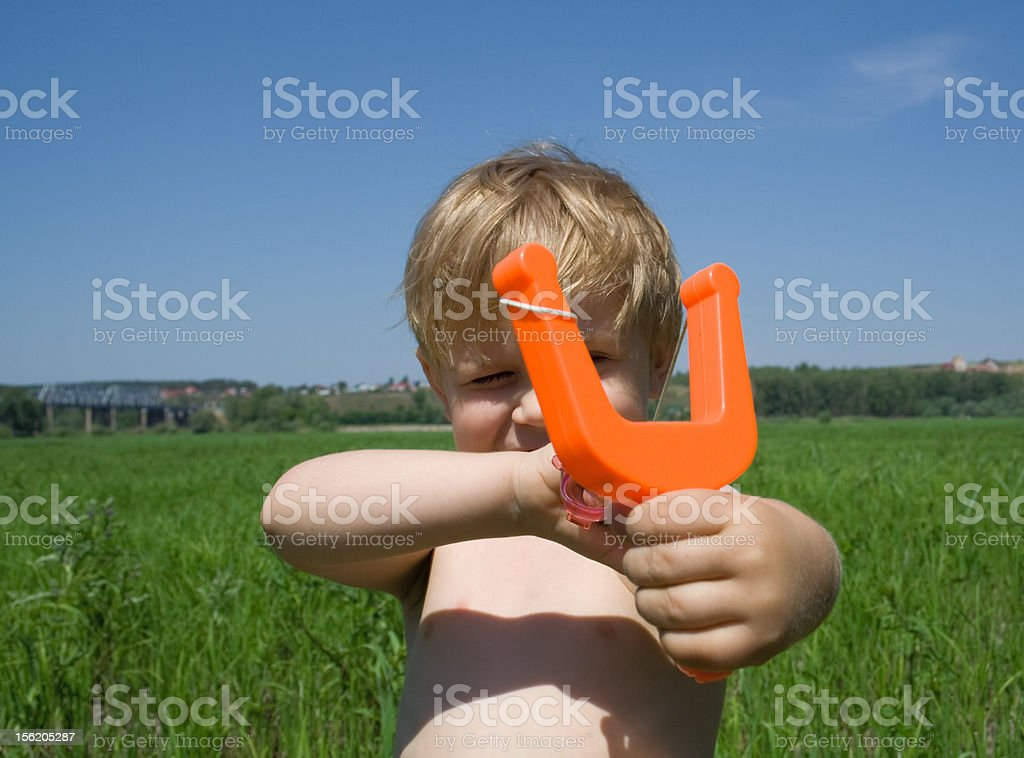 Boy aims from a slingshot royalty-free stock photo