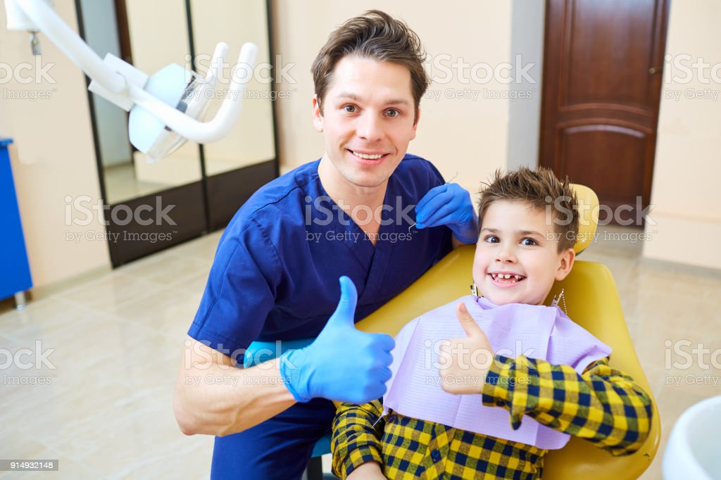 A boy and a dentist man in a dental office stock photo