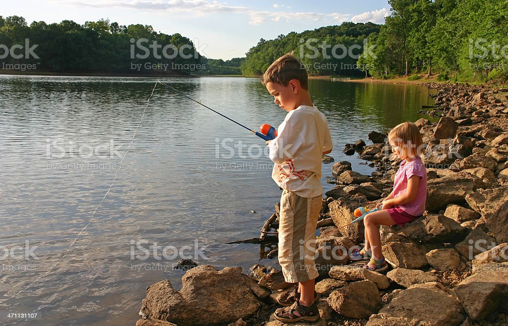 A boy and a girl fishing in a lake close to a forest royalty-free stock photo