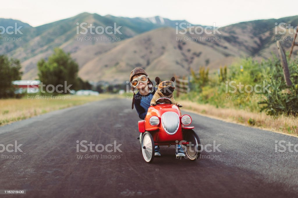 Boy and Dog in Toy Racing Car A young boy with flying goggles and flight cap races a red toy car with his pet and best friend French Bulldog along a small road in Utah, USA. Sometimes a road trip journey with your best friend and some fresh air in your face is the best medicine for the soul. Adventure Stock Photo