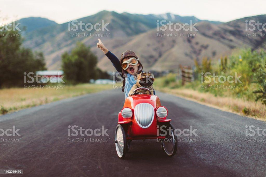 Junge und Hund in Spielzeug Racing Car - Lizenzfrei Abenteuer Stock-Foto