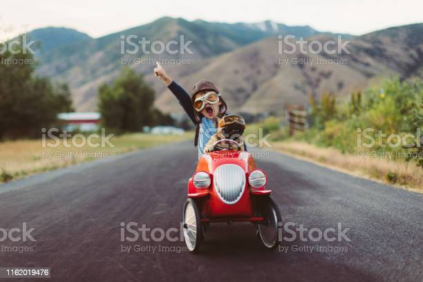 Photo of Boy and Dog in Toy Racing Car