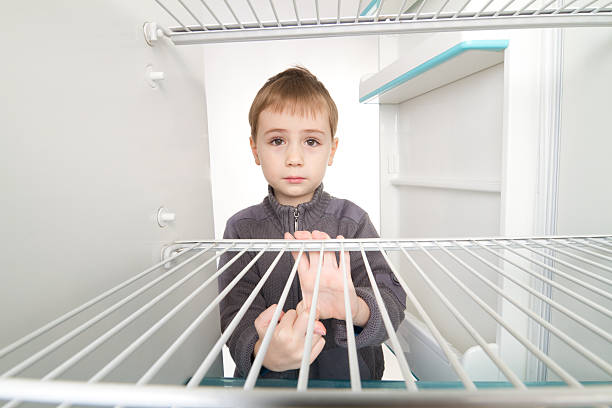 Boy and Empty Refrigerator Boy looking into empty refrigerator. hungry stock pictures, royalty-free photos & images