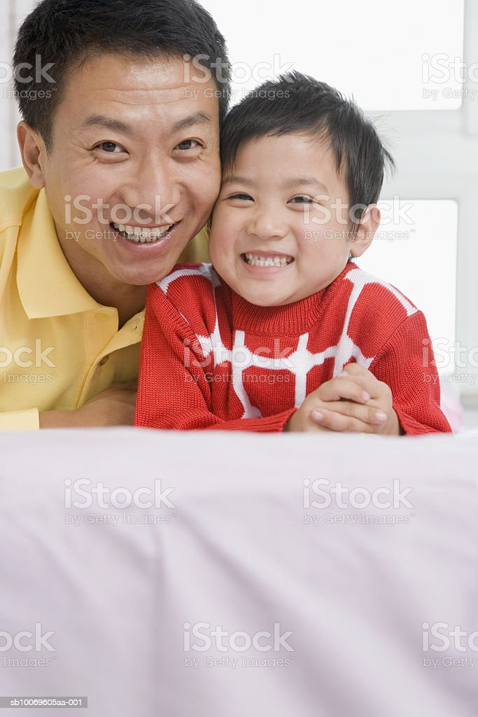 Boy (4-5) and father lying on bed, smiling, portrait royalty-free 스톡 사진