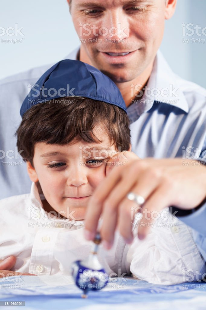 Boy and father playing with dreidl stock photo