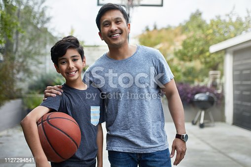 Portrait of happy boy and father standing at basketball court. Mid adult man and child are in casuals at yard. They are smiling.