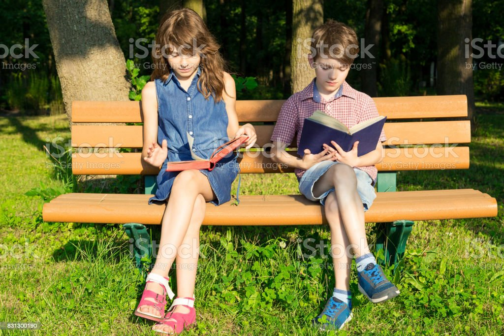 Boy and girl are sitting on a bench in the park and reading books. stock photo
