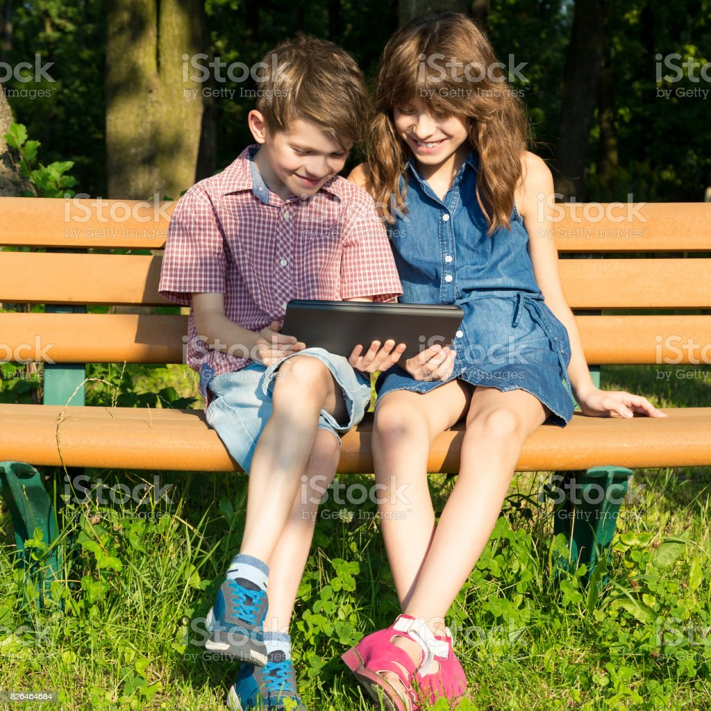 Boy and girl are sitting on a bench in the park, looking at the tablet and smiling. stock photo
