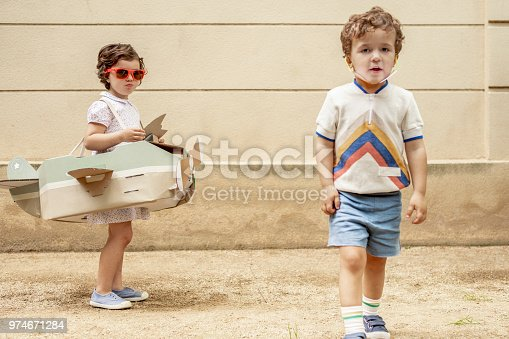 istock Boy and girl arguing over airplane 974671284