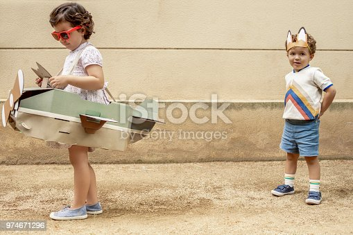 istock Boy and girl arguing over airplane 974671296