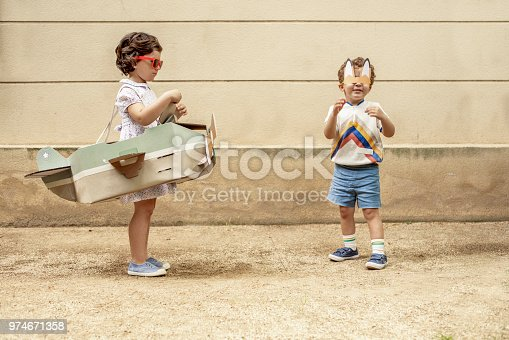 istock Boy and girl arguing over airplane 974671358