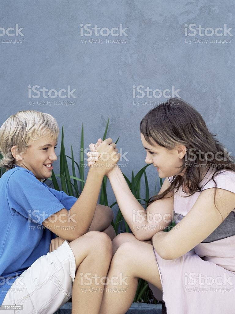 Boy and girl arm wrestling royalty-free 스톡 사진
