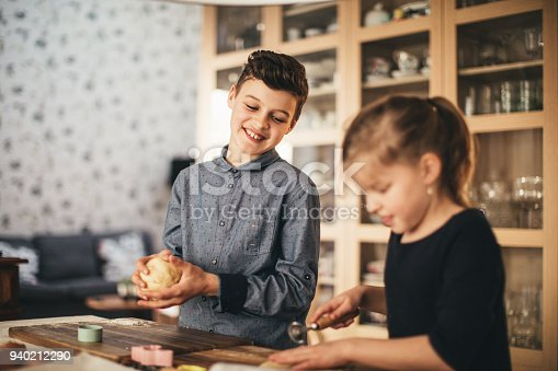 664420980 istock photo boy and girl baking cookies on the kitchen desk while having a lot of fun 940212290