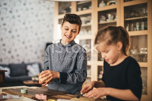 664420980istockphoto boy and girl baking cookies on the kitchen desk while having a lot of fun 940213220