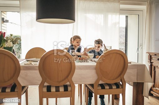 664420980istockphoto boy and girl baking cookies on the kitchen desk while having a lot of fun 940214392