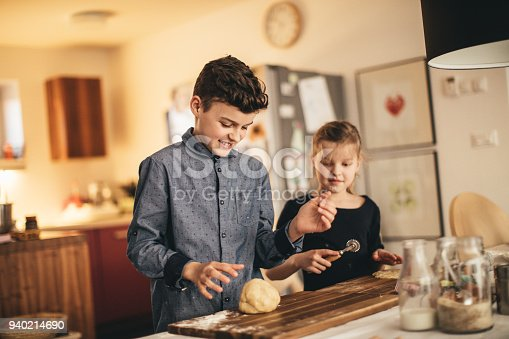 istock boy and girl baking cookies on the kitchen desk while having a lot of fun 940214690