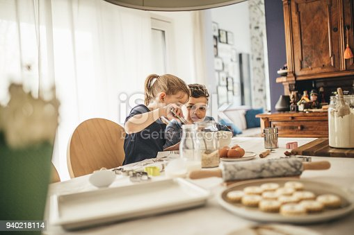 664420980istockphoto boy and girl baking cookies on the kitchen desk while having a lot of fun 940218114