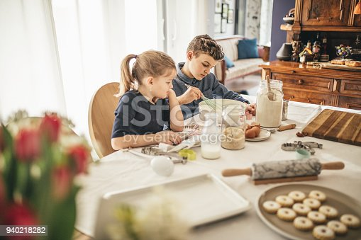 664420980istockphoto boy and girl baking cookies on the kitchen desk while having a lot of fun 940218282
