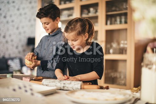 istock boy and girl baking cookies on the kitchen desk while having a lot of fun 940226270