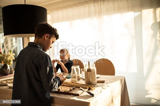 664420980istockphoto boy and girl baking cookies on the kitchen desk while having a lot of fun 940226368