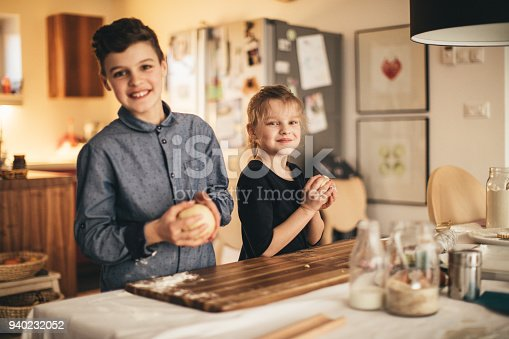 istock boy and girl baking cookies on the kitchen desk while having a lot of fun 940232052