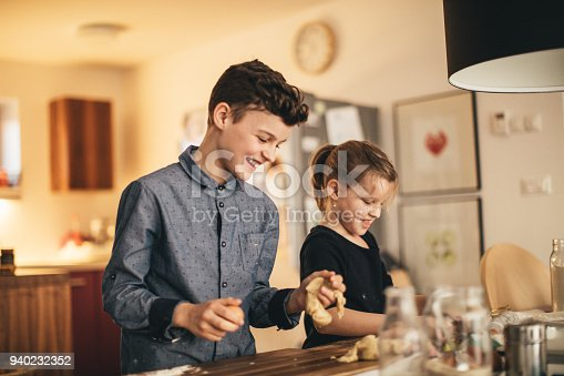 istock boy and girl baking cookies on the kitchen desk while having a lot of fun 940232352