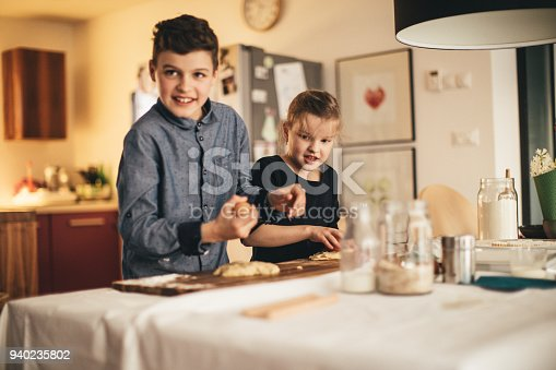664420980 istock photo boy and girl baking cookies on the kitchen desk while having a lot of fun 940235802