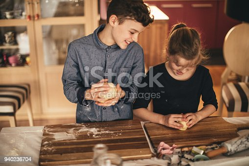 664420980 istock photo boy and girl baking cookies on the kitchen desk while having a lot of fun 940236704