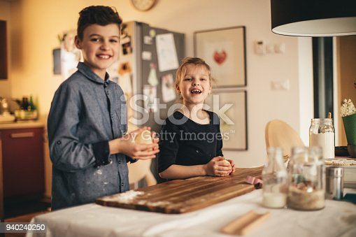 664420980istockphoto boy and girl baking cookies on the kitchen desk while having a lot of fun 940240250