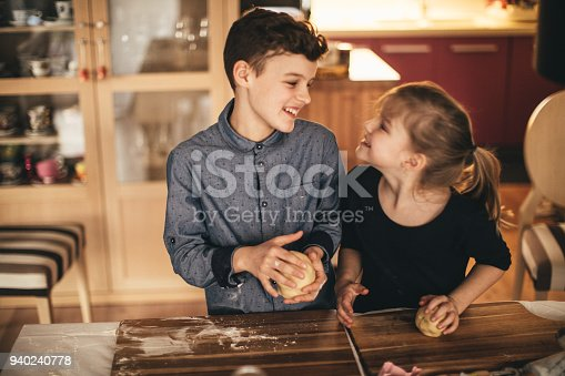 664420980istockphoto boy and girl baking cookies on the kitchen desk while having a lot of fun 940240778