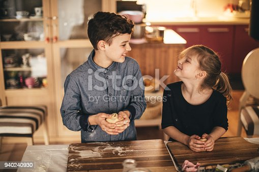 664420980 istock photo boy and girl baking cookies on the kitchen desk while having a lot of fun 940240930