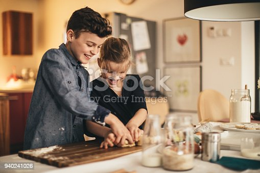 istock boy and girl baking cookies on the kitchen desk while having a lot of fun 940241026